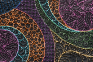 This is a close up of The Trip. This is really a modern take on a quilt classic called a Whole Cloth Quilt.  The surface of this quilt is a solid black fabric. All the color is simply thread. Each color has its own motif or doodle.