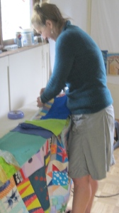Here I am ironing the quilt out in McCarthy. At this point, I was still having to fire up a generator to iron. I now hove enough solar power to iron and stitch off the grid!