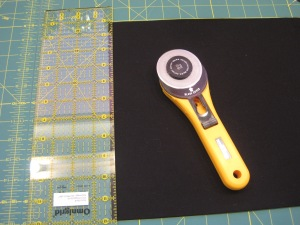"Next I use the straight edge of the ruler to finish the edge of my fabric off. Essentially I am cutting away in rough edges. My favorite Ruler is a  Olfa $' x 16"" and my favorite cutter is a Olfa 45mm with an old school handle."