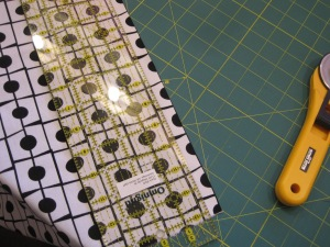 "I want to isolate on row of the dots. To do this, I must cut 1/4"" from away from the actual area I want to show up in my quilt. I line the 1/4"" up with the black line on the fabric and begin to cut."