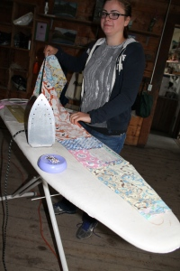 Andrea at the ironing board making curtains for her grandmother's 1920's cabin in downtown McCarthy.