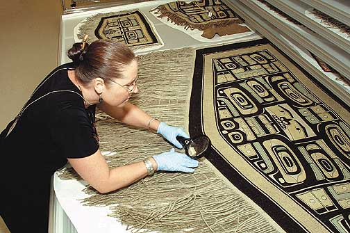 **SPECIAL MCCLATCHY-ANCHORAGE**Alaskan artist Teri Rofkar examines woven artifacts at the Smithsonian's National Museum of the American Indian Cultural Resource Center in Suiteland, Maryland, Tuesday, March 18, 2003. (AP Photo/Adele Starr)